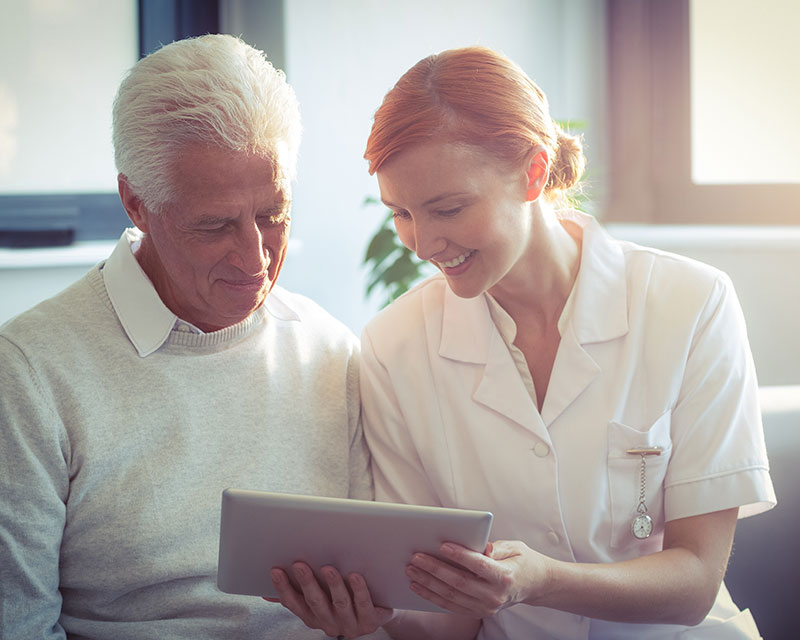 Image of a nurse showing an older man his medical records on a tablet