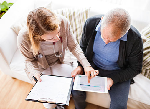 Image of a medical professional showing an older man his records on a tablet and cllipboard